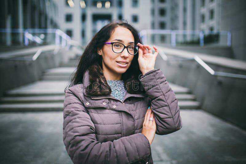 Брюнет бизнес-леди портрета красивое молодое в куртке и свитере стоит на офисном здании предпосылки, деловом центре в gl стоковая фотография rf