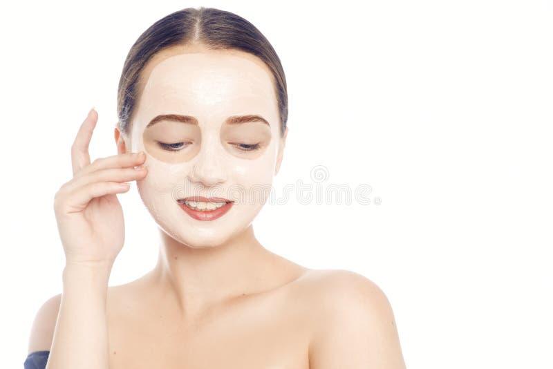 Брюнет в белой маске для стороны Красивое фото девушки с идеальной кожей Маленькая девочка заботит для себя r стоковые изображения
