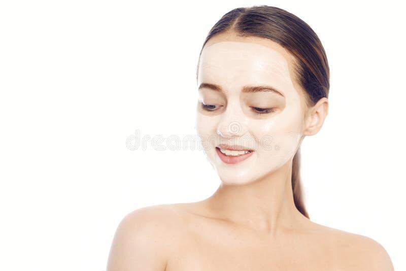 Брюнет в белой маске для стороны Красивое фото девушки с идеальной кожей Маленькая девочка заботит для себя r стоковое фото rf