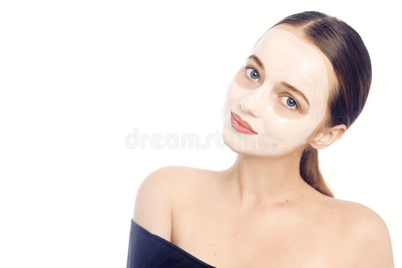 Брюнет в белой маске для стороны Красивое фото девушки с идеальной кожей Маленькая девочка заботит для себя r стоковая фотография rf