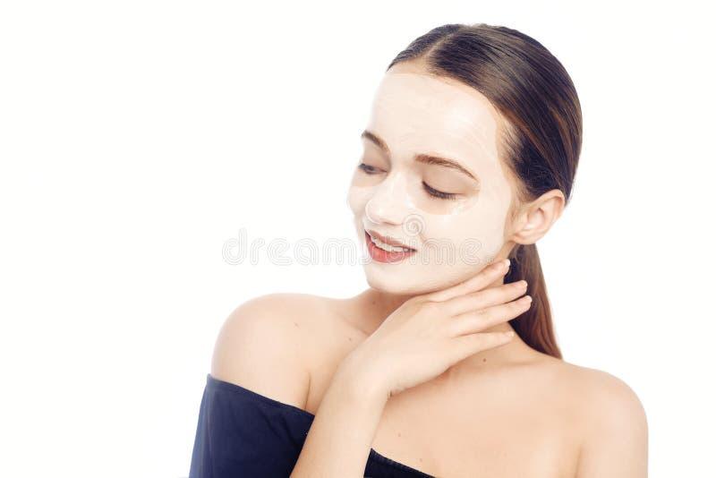 Брюнет в белой маске для стороны Красивое фото девушки с идеальной кожей Маленькая девочка заботит для себя r стоковое фото