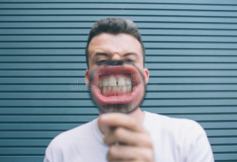 Брюнет в белой рубашке стоит на стене и представлять Он держит loup в руке и показывает его зубы на камере ванта стоковое фото rf