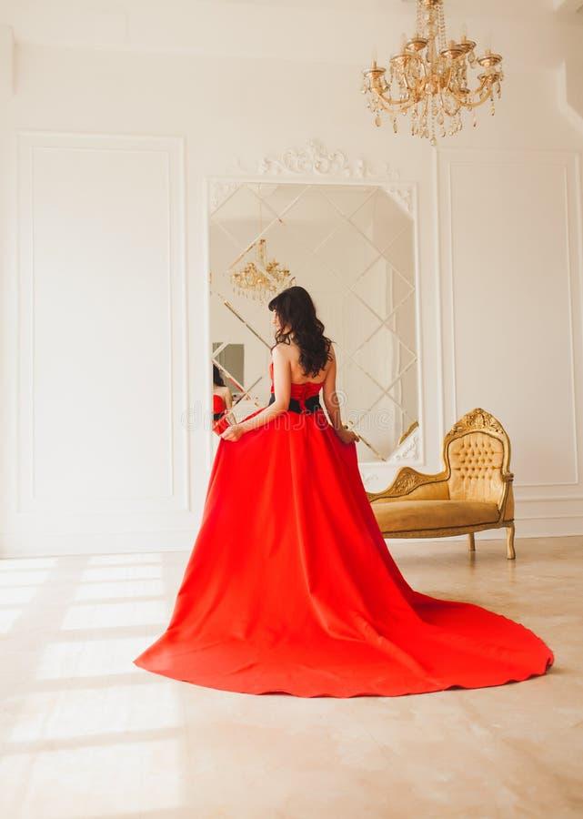 Брюнет в длинном красном платье стоковое фото