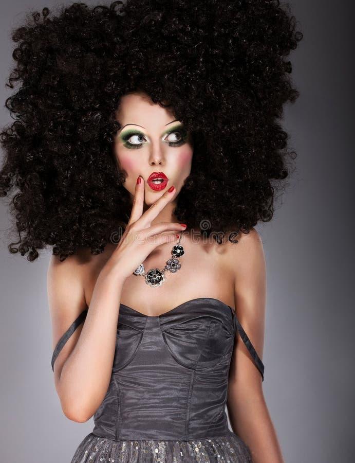 Брюнет в парике искусства гримасничая. Творческая концепция стоковые фото