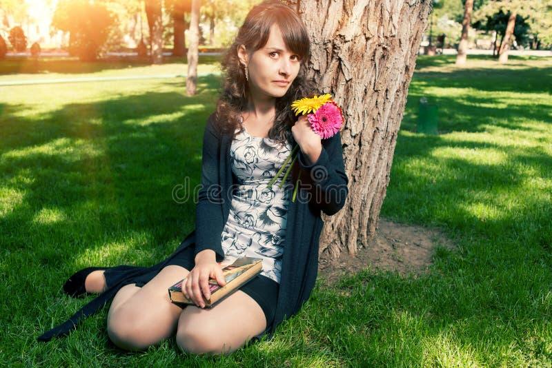Брюнет в платье сидя на траве около дерева стоковая фотография rf
