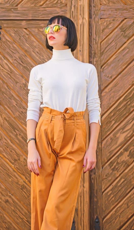 Брюнет женщины модный стоит outdoors деревянная предпосылка Девушка с макияжем представляя внутри стоковые изображения rf