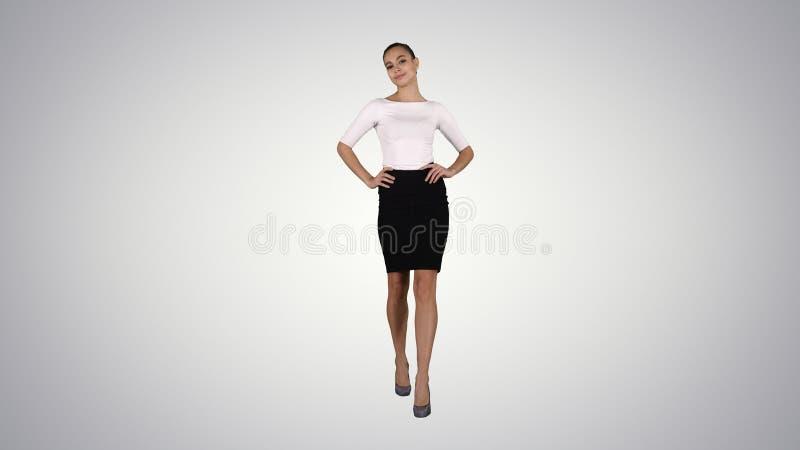 Брюнет женщины моды очарования идя уверенно на предпосылку градиента стоковое изображение rf