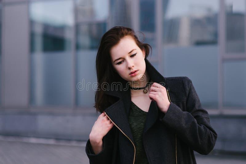Брюнет женщины стильного внешнего портрета красивое одело в черноте и предпосылке серого цвета города предпосылки стоковое изображение rf