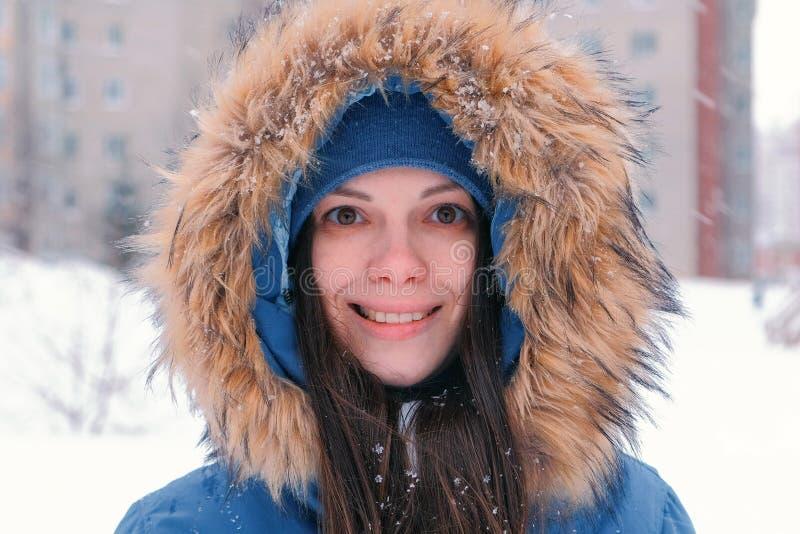 Брюнет молодой женщины смотря камеру и усмехаться Нося синь вниз с куртки с клобуком меха, концом-вверх стороны стоковая фотография