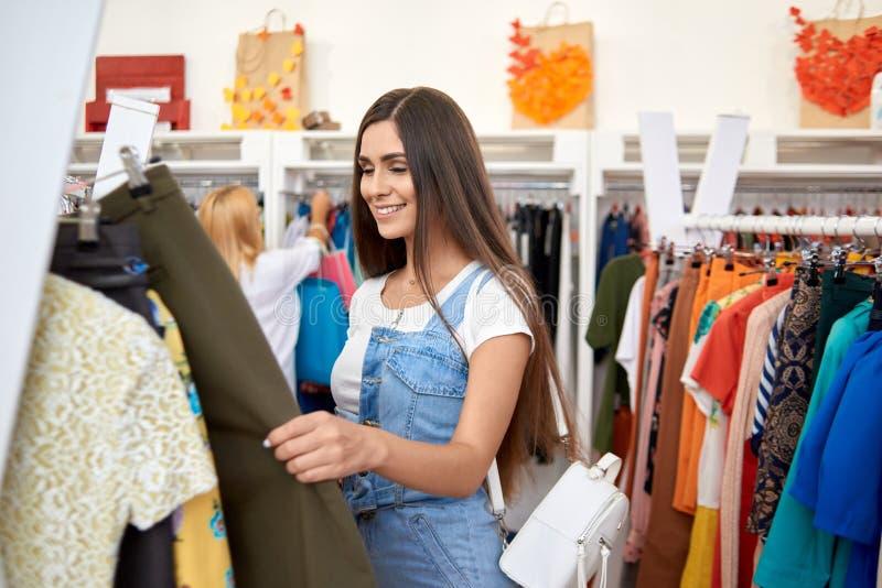 Брюнет отдыхая и ходя по магазинам в магазине одежды стоковая фотография