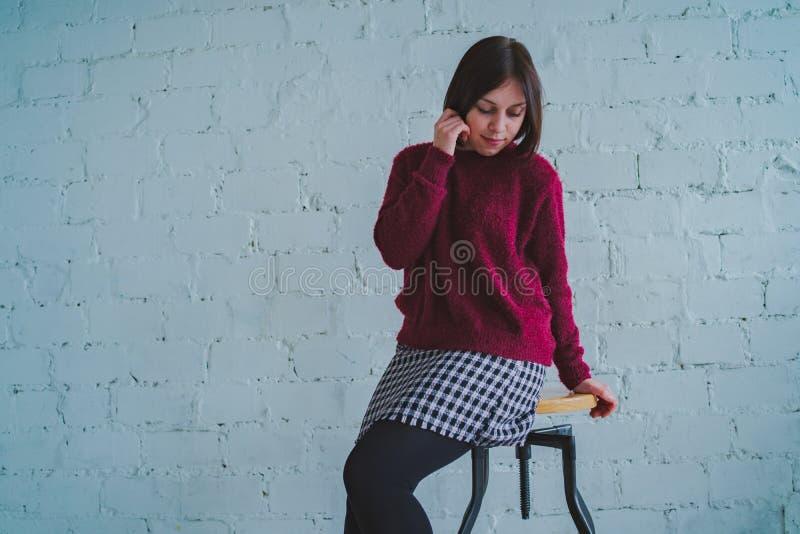 Брюнет представляя со стулом, против кирпичной стены стоковое изображение