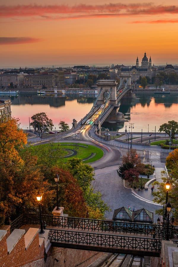 Будапешт, Венгрия - известный мост Lanchid и Clark Адам Szechenyi цепной придает квадратную форму карусели на восходе солнца стоковые изображения rf