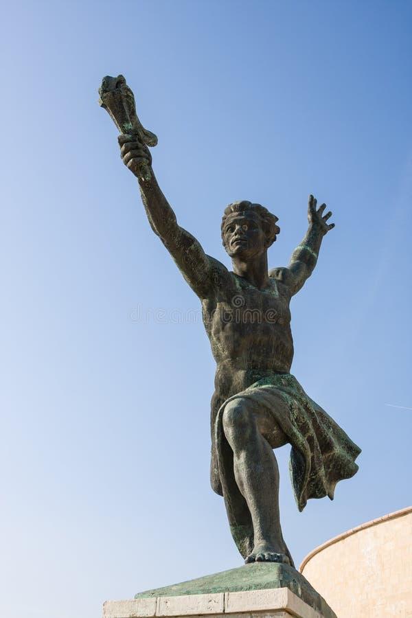 Будапешт, Венгрия - 6-ое ноября 2017: Человек с статуей факела рядом с памятником свободы на верхней части холма Gellert стоковые изображения rf