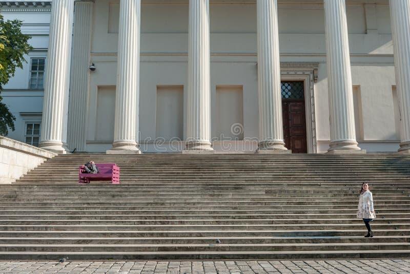 БУДАПЕШТ, ВЕНГРИЯ - 26-ОЕ ОКТЯБРЯ 2015: Дворец Будапешта при местные люди сидя на красочных стенде и читать Азиатский турист стоковая фотография rf