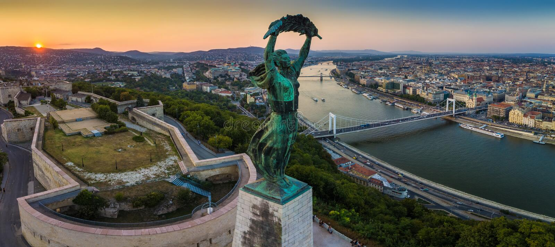 Будапешт, Венгрия - панорамный взгляд венгерской статуи свободы на восходе солнца с мостом Elisabeth и мостом Szechenyi цепным стоковое фото rf