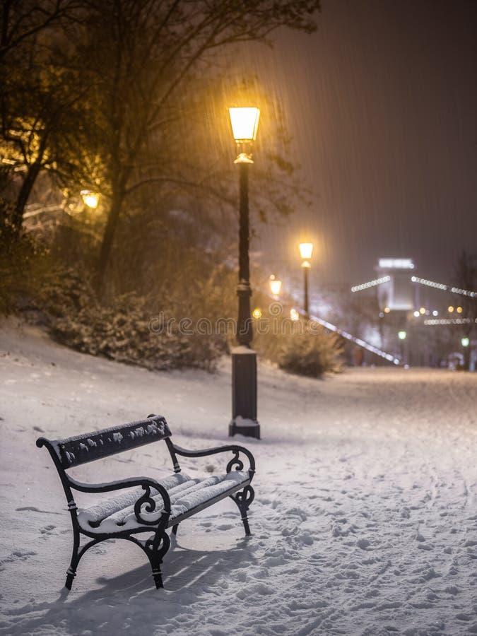 Будапешт, Венгрия - столб Суда и лампы в снежном парке на районе Buda с мостом Szechenyi цепным на предпосылке во время идти снег стоковое изображение rf