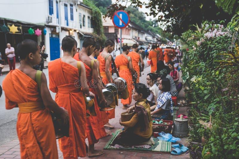 Буддийские милостыни давая церемонию в утре Традиция давать милостыни к монахам в Luang Prabang была расширена к туристам стоковые изображения