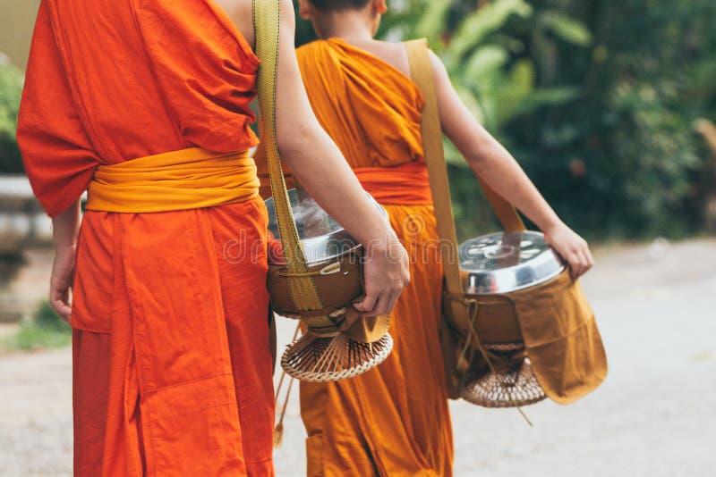 Буддийские монахи во время лаосских традиционных священных милостынь давая церемонию в городе Luang Prabang, Лаосе стоковые фото