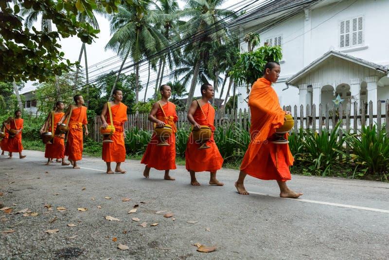 Буддийские монахи собирая милостыни в Luang Prabang, Лаосе стоковые изображения