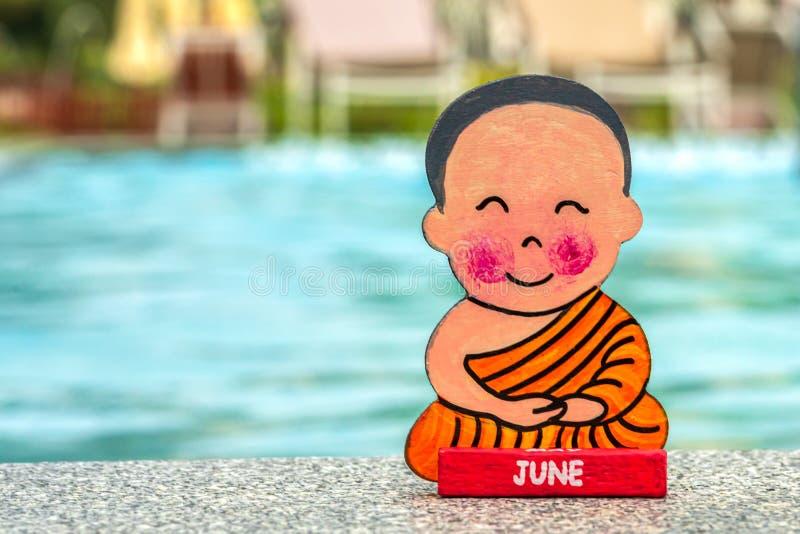 Буддийский мальчик на каникулах сидя летом положения лотоса счастливым на крае бассейна E подпишите с стоковая фотография
