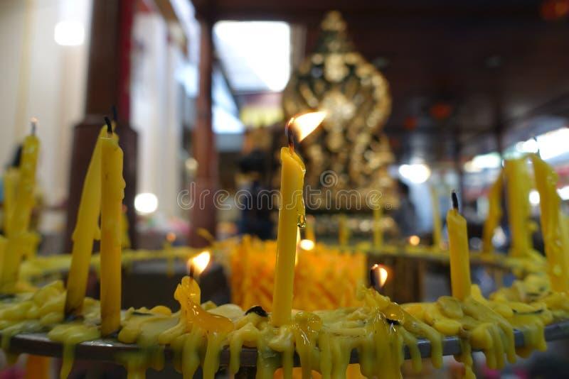Буддисты делают заслугу, устанавливающ освещенную свечу и осветили ладан с рамкой свечей на алтаре Будды на виске селективно стоковые изображения
