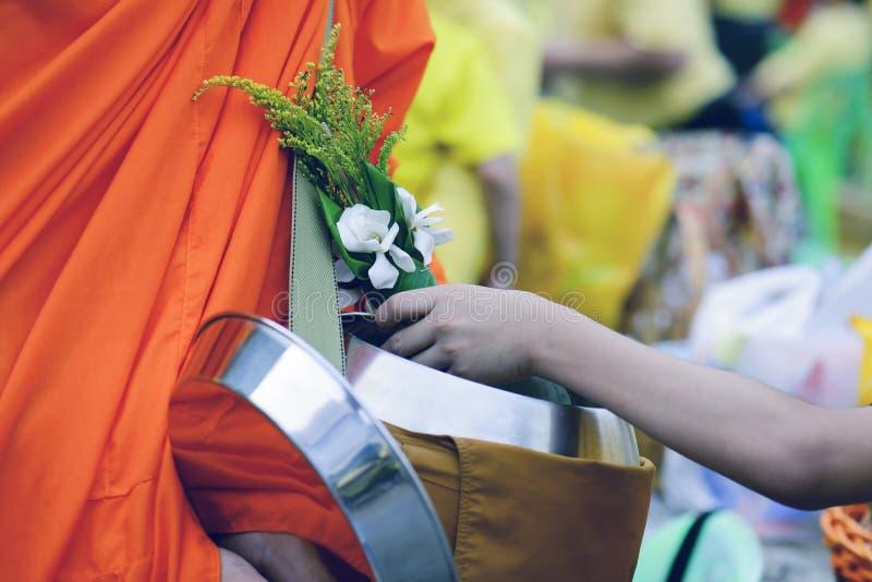 Буддисты приносят еду и цветки к монахам для того чтобы сделать заслугу для монахов согласно буддийским убеждениям стоковые изображения