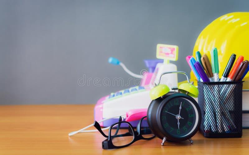 Будильник, зрелища, ручки цвета, книги, трудная шляпа и банкомат игрушки на деревянном столе стоковое изображение