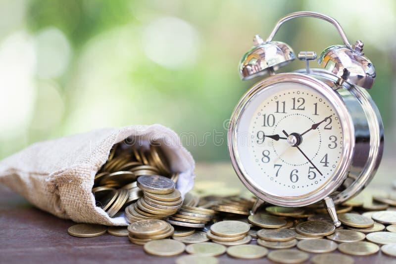 Будильник и куча золотых монеток на таблице, концепции времени возможных издержек и сбережений денег Инвестиционный риск стоковые изображения