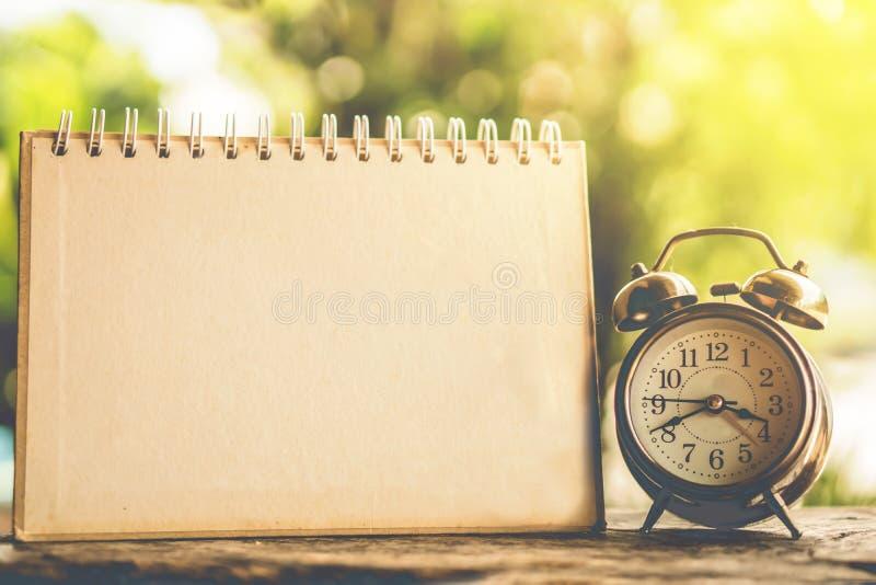 Будильник и пустая страница календаря на деревянной предпосылке стоковая фотография rf