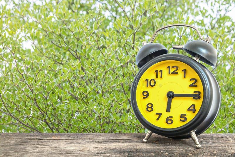 Будильник крупного плана черный и желтый для украшает выставку квартал за 6 или 6:15 a M на старом коричневом деревянном столе на стоковые изображения