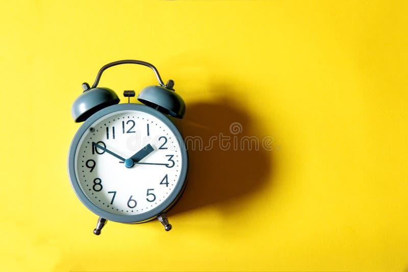 Будильник на яркой желтой предпосылке, жулик контроля времени стоковые фотографии rf