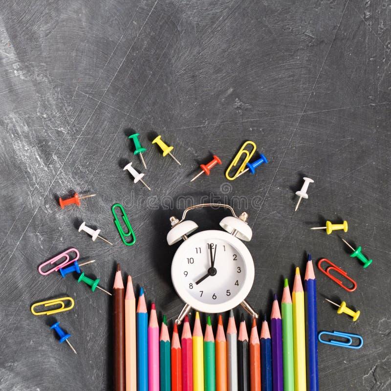 Будильник, покрашенные карандаши и канцелярские принадлежности на черной предпосылке школьного правления стоковое изображение rf