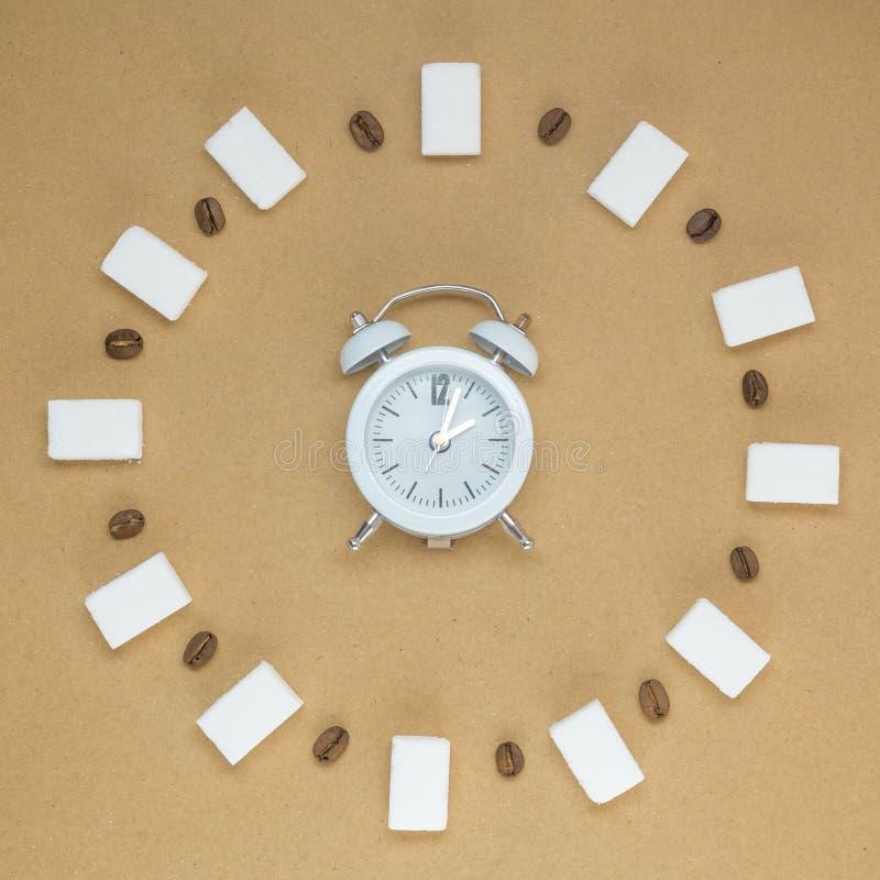 Будильник с кофейными зернами и кубами сахара Концепция питья Minimalistic горячая сладостная стоковые фотографии rf