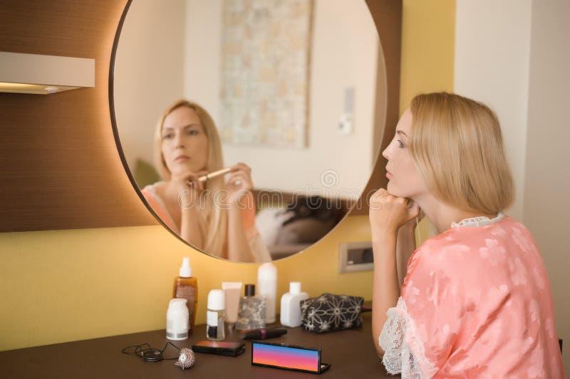 Будуар в спальне с косметиками Красивая молодая женщина сидит внимательно перед отражением в зеркале стоковая фотография