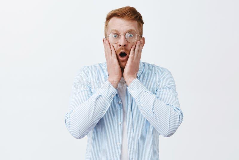 Будучи сотрясенным человек видящ ужасную сцену Портрет оглушенного ужаснутого мужчины redhead в падать стекел и рубашек стоковое фото rf
