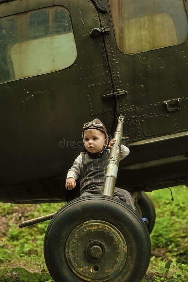 Будущая профессия Ребенок сидя на колесах вертолета стоковое изображение rf
