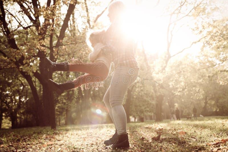 Будьте матерью держать дочь и вращайте в круге стоковая фотография