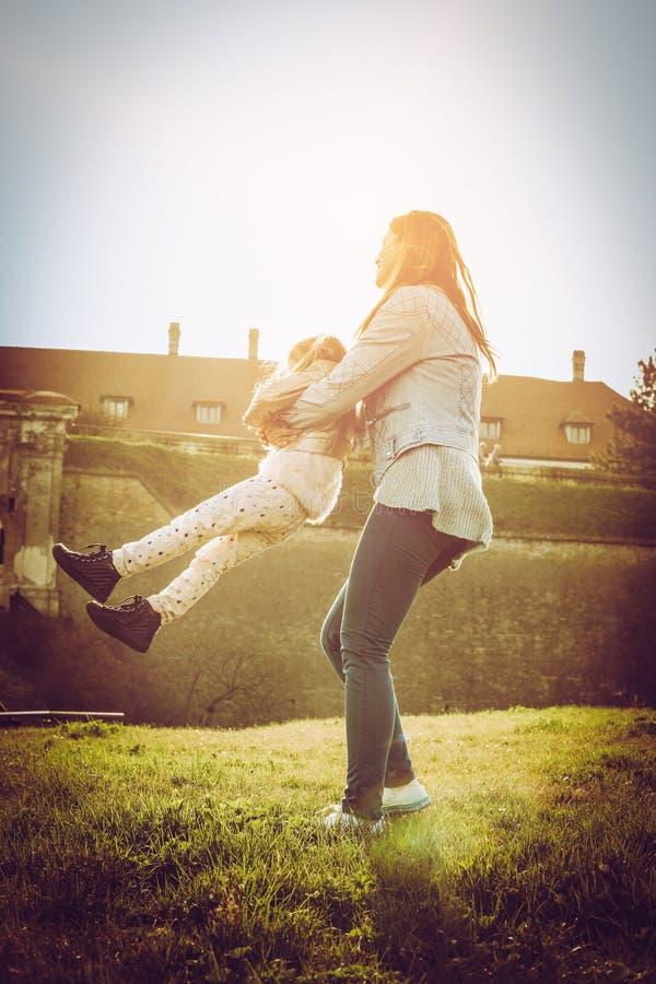 Будьте матерью играть с ее дочерью в парке Мать поворачивает ее стоковое изображение