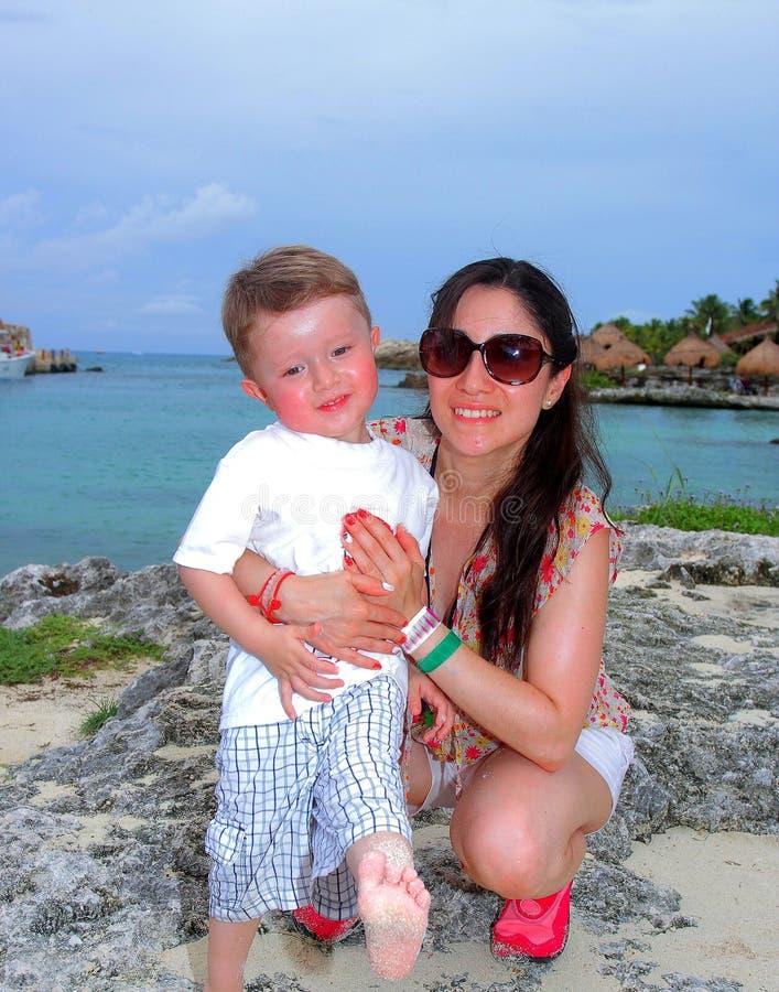 Будьте матерью и ее молодой сын, на пляже на заходе солнца стоковые изображения rf
