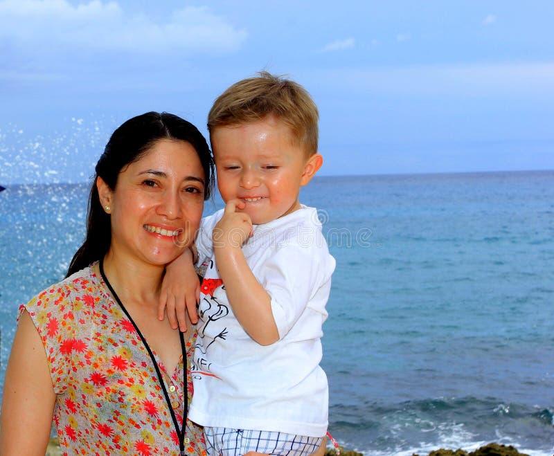 Будьте матерью и ее молодой сын, на пляже на заходе солнца стоковое фото rf