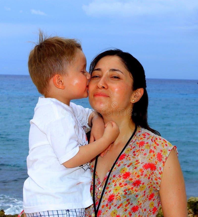 Будьте матерью и ее молодой сын, на пляже на заходе солнца стоковая фотография