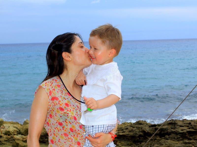Будьте матерью и ее молодой сын, на пляже на заходе солнца стоковые изображения