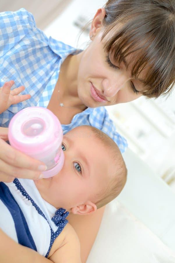 Будьте матерью подавая младенца младенца младенца есть молоко от бутылки стоковое изображение