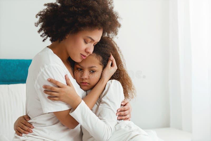 Будьте матерью утешать ее дочь, сидя в спальне стоковое фото rf
