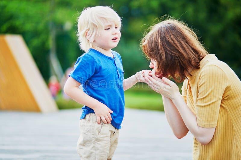 Будьте матерью утешать ее сына после того как он раненый его рука стоковое изображение rf