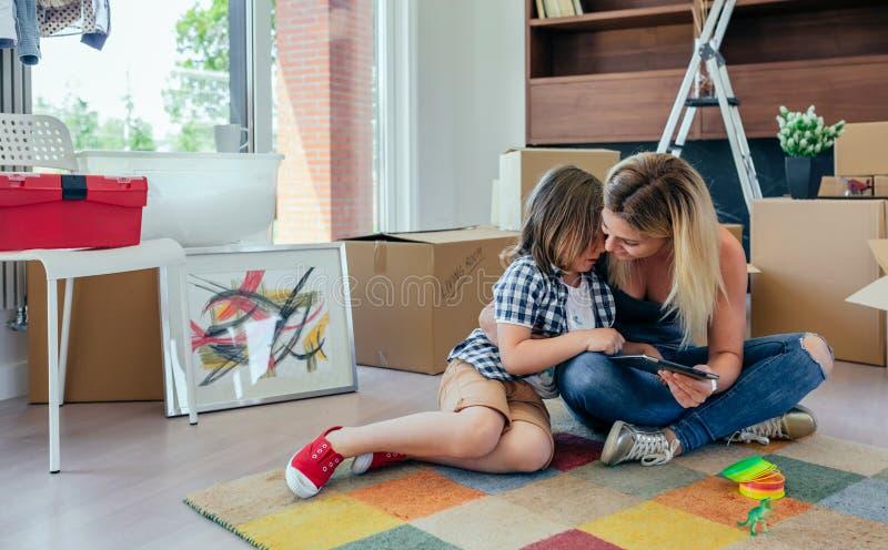 Будьте матерью утешать ее унылого сына сидя на ковре стоковые фотографии rf