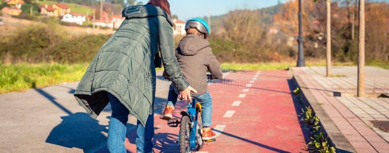 Будьте матерью уча сына для того чтобы ехать велосипед в cycleway стоковая фотография
