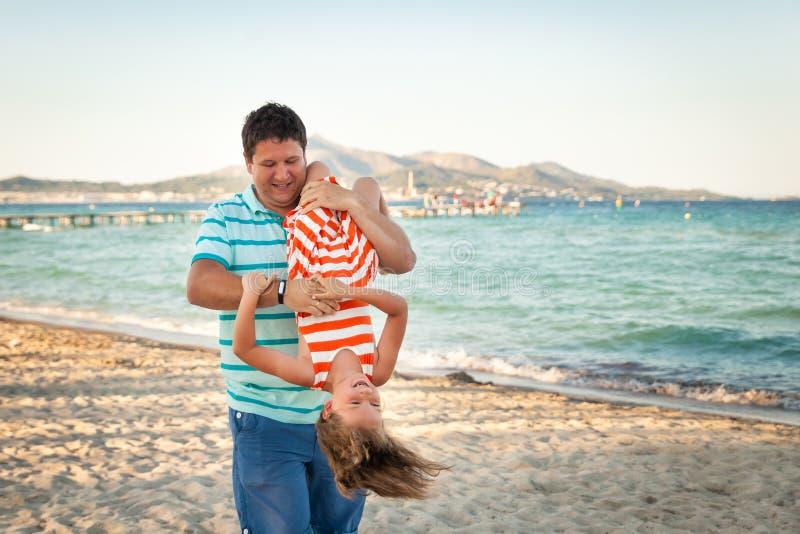 Будьте отцом играть с его дочерью на пляже вечера стоковое фото rf