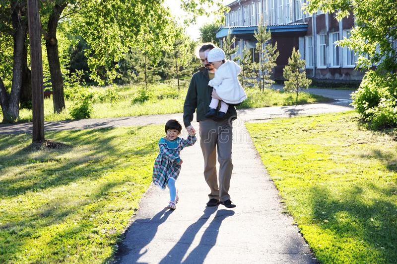 Будьте отцом идти в парк с дочерьми на солнечном дне стоковые изображения