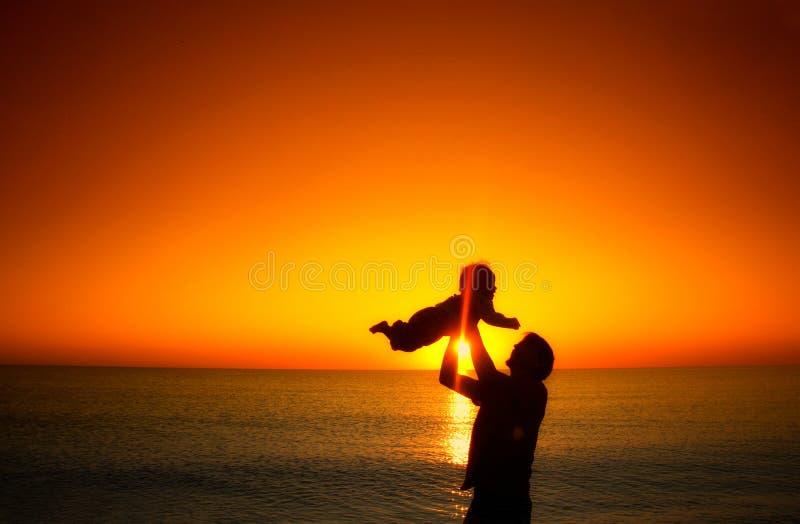 Будьте отцом и его маленькая игра сына младенца на пляже захода солнца Vaca семьи стоковое изображение